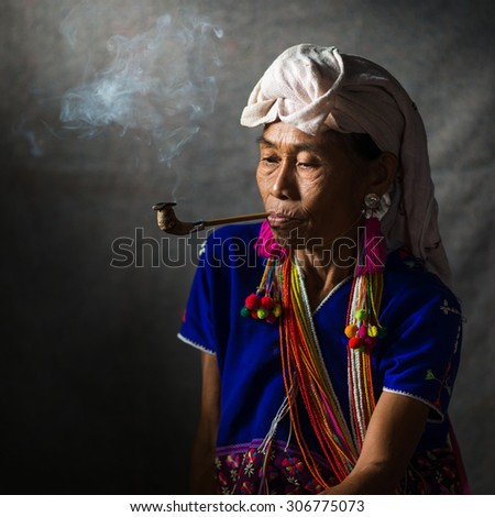 CHIANG MAI, THAILAND - JUL 25 : Karen hill tribe is smoking tobacco pipe with traditional clothes and dramatic light on July 25, 2015 in Chiang Mai, Thailand. - stock photo