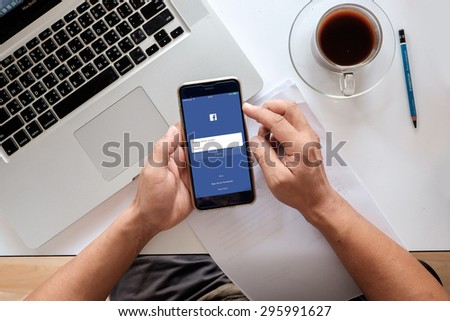 CHIANG MAI ,THAILAND - JULY 13, 2015: Young man touch Facebook icons on Apple iPhone 6 plus. Facebook is largest and most popular social networking site in the world.  - stock photo