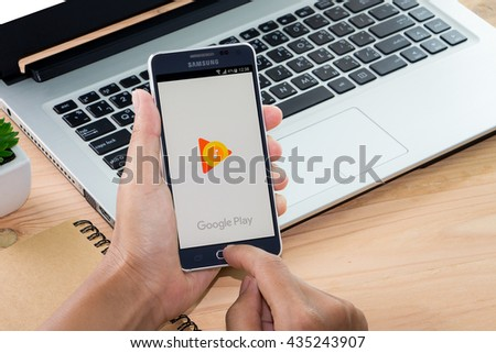 CHIANG MAI,THAILAND - JUN 12, 2016 : Woman holding Samsung galaxy Alpha with google play music app on the screen on Wood desk office. Top view of Business workplace. - stock photo