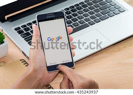 CHIANG MAI,THAILAND - JUN 12, 2016 : Woman holding Samsung galaxy Alpha with google search app on the screen on Wood desk office. Top view of Business workplace. - stock photo