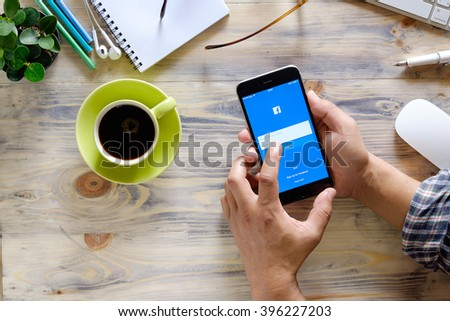CHIANG MAI,THAILAND - MAR 26, 2016 : Young man touch Facebook icons on Apple iPhone 6 plus. Facebook is largest and most popular social networking site in the world.  - stock photo