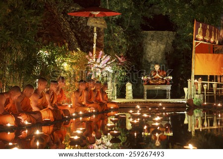 CHIANG MAI THAILAND - MARCH 4 :Magha Puja Day is the important Buddhist holiday. Buddhist monk fire candles to the Buddha. Mar 4,2015 in Phan Tao Temple, Chiangmai, Thailand. - stock photo