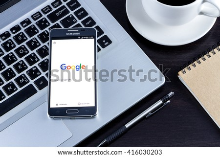 CHIANG MAI,THAILAND - MAY 06, 2016 : Samsung galaxy Alpha with google search app on the screen lying on wood desk office. Top view of Business workplace. - stock photo