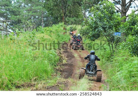 CHIANG MAI, THAILAND - NOVEMBER 23 : Tourists riding ATV to nature adventure on dirt track on NOVEMBER 23, 2013 in Chiang Mai, Thailand.  - stock photo