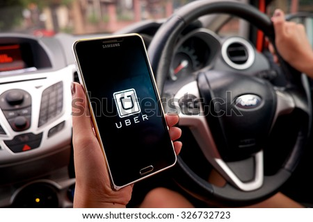 CHIANG MAI,THAILAND - SEP 16,2015 : A woman hand holding Uber app showing on Samsung note 3 in the car,Uber is smartphone app-based transportation network.  - stock photo
