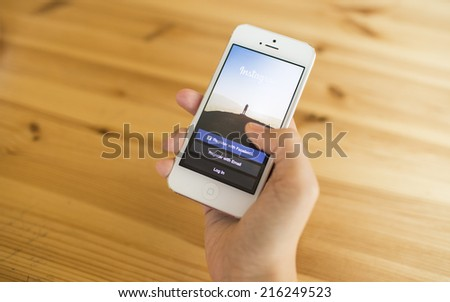 CHIANG MAI, THAILAND - SEPTEMBER 07, 2014: A girl trying to log in Instagram application using Apple iPhone 5. Instagram is largest and most popular photograph social networking site in the world. - stock photo
