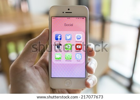 CHIANG MAI, THAILAND - SEPTEMBER 07, 2014: All of popular social media icons on smartphone device screen with hand holding on Apple iPhone 5. - stock photo
