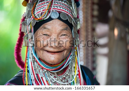 CHIANG RAI, THAILAND - DEC 4: Unidentified Akha tribe elderly woman with traditional clothes and silver jewelery in hill tribe minority village on December 4, 2013. Mae Hong Son, Thailand.  - stock photo