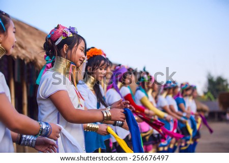 CHIANG RAI, THAILAND - JANUARY 2015: Karen tribal girls dressed in traditional costumes  performing national dance in Padaung long neck hill tribe village community originate from neighboring Myanmar. - stock photo