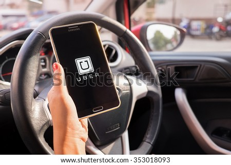 CHIANGMAI,THAILAND - DEC 16,2015 : A woman hand holding Uber app showing on Samsung note 3 in the car,Uber is smartphone app-based transportation network. - stock photo