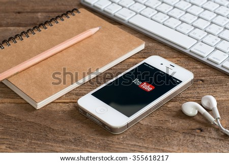 CHIANGMAI,THAILAND - December 28, 2015: Selective focus Brand Apple iPhone 4s with YouTube app on the screen lying on desk with headphones. YouTube is the popular online video-sharing website, - stock photo