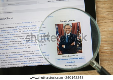 CHIANGMAI, THAILAND - February 26, 2015: Photo of Wikipedia article page about Barack Obama on a ipad monitor screen through a magnifying glass. - stock photo