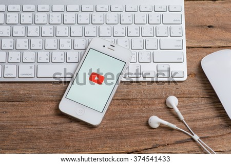 CHIANGMAI, THAILAND - February 10, 2016 :Selective focus Brand Apple iPhone 4s with YouTube app on the screen lying on desk with headphones. YouTube is the popular online video-sharing website, - stock photo