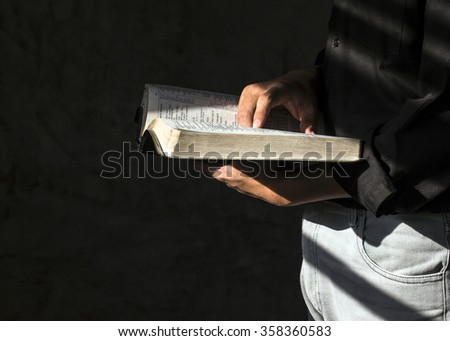 CHIANGMAI, THAILAND - Jan 2, 2016. A man hands holding and reading to  the open bible (New International Version) in the dark room against the light from windows, Christian concept - stock photo