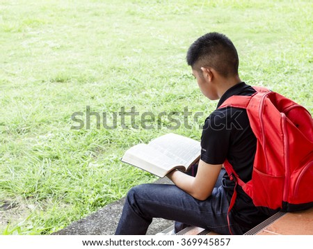 CHIANGMAI, THAILAND - Jan 25, 2016. A young man is reading the bible (New International Version) at the terrace for his devotional in the morning, Christian concept - stock photo