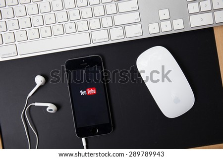 CHIANGMAI, THAILAND -JUNE 23, 2015:Brand new Apple iPhone with YouTube app on the screen lying on desk with headphones. YouTube is the popular online video-sharing website, - stock photo