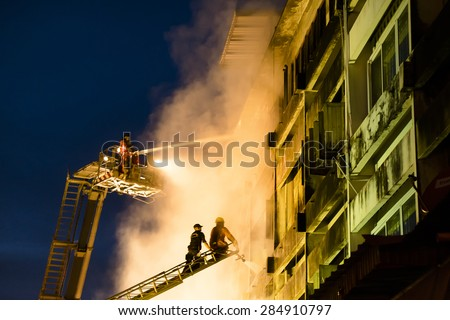 CHIANGMAI THAILAND - JUNE 5 : Warorot market fire. Firefighters were spraying water to extract the fire from spreading to adjacent buildings. on June 5 , 2015 in Chiang Mai,Thailand. - stock photo