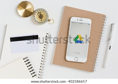 CHIANGMAI,THAILAND - MAR 01, 2016 : Google Drive showing on Apple iPhone 6s screen display put on brown bookpaper. Google Drive is a free online file storage. - stock photo