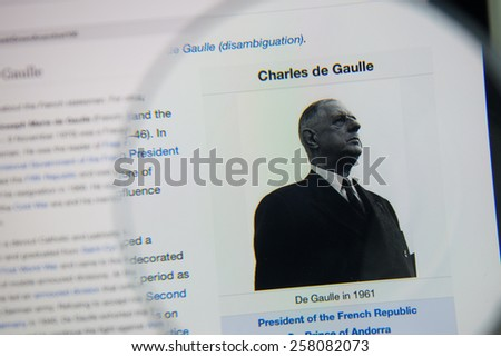 CHIANGMAI, THAILAND - March 5, 2015: Photo of Wikipedia article page of Charles de Gaulle on a ipad monitor screen through a magnifying glass. - stock photo