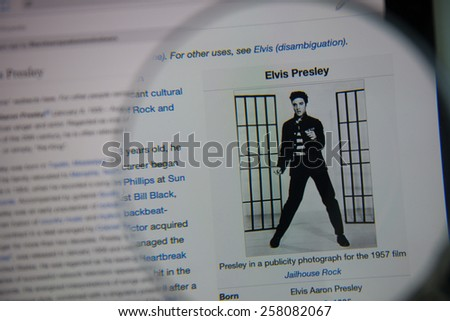 CHIANGMAI, THAILAND - March 5, 2015: Photo of Wikipedia article page of Elvis Presley on a ipad monitor screen through a magnifying glass. - stock photo