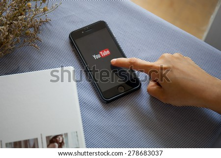 CHIANGMAI, THAILAND -MAY 17, 2015:Brand new Apple iPhone 6 with YouTube app on the screen lying on desk with headphones. YouTube is the popular online video-sharing website, - stock photo
