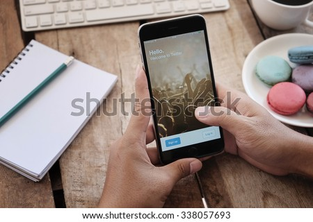"""CHIANGMAI, THAILAND -NOV 2,2015:A man hold Apple iPhone 6 plus open Twitter application,Twitter is an online social networking and microblogging service that enables users to send and read """"tweets""""  - stock photo"""