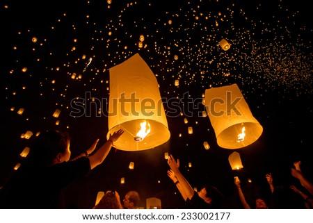 CHIANGMAI, THAILAND - NOV 16: People release sky lanterns to worship Buddha's relics during Yi Peng festival on November 16, 2013 in Chiangmai, Thailand - stock photo