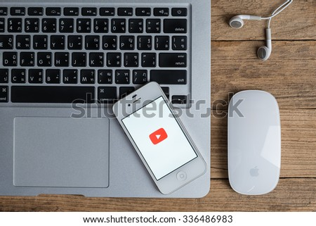 CHIANGMAI,THAILAND - November 08, 2015: Brand Apple iPhone 4s with YouTube app on the screen lying on desk with headphones. YouTube is the popular online video-sharing website, - stock photo