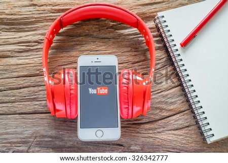 CHIANGMAI, THAILAND -OCTOBER 12, 2015:Brand new Apple iPhone with YouTube app on the screen lying on desk with headphones. - stock photo