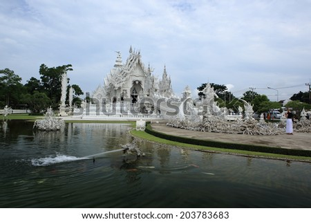 Chiangrai ,Thailand -July 5, 2014 : Wat Rong Khun more well-known as the White Temple, is contemporary unconventional Buddhist temple in Chiang Rai Province, designed by Chalermchai Kositpipat in 1997 - stock photo
