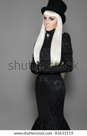 Chic aristocratic woman in retro style black dress and beaver hat. Long blond straight hairstyle - stock photo