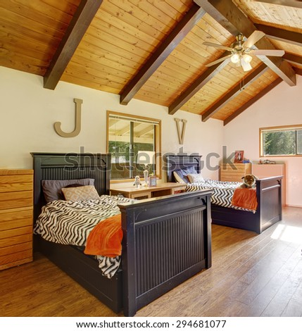 Chic kids room with twin beds, vaulted ceiling, and hardwood floor. - stock photo