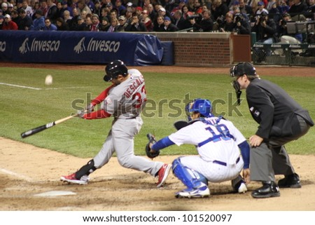 CHICAGO - APRIL 25: Daniel Descalso of the St. Louis Cardinals hits a ball during a game against the Chicago Cubs at Wrigley Field on April 25, 2012 in Chicago, Illinois. - stock photo