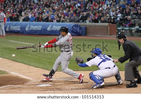 CHICAGO - APRIL 25: Skip Schumaker of the St. Louis Cardinals hits a ball during a game against the Chicago Cubs at Wrigley Field on April 25, 2012 in Chicago, Illinois. - stock photo
