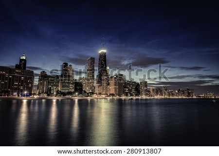 Chicago Downtown skyscrapers with reflections in Lake Michigan at night - stock photo
