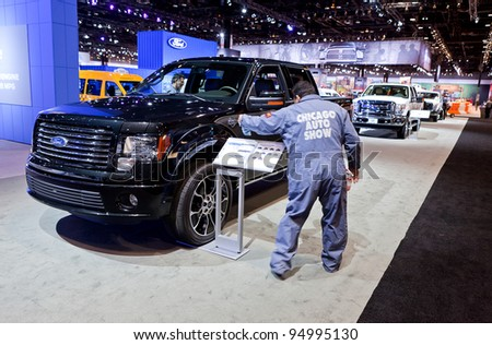 CHICAGO - FEB 8: Workers prep the cars for the show opening on display at the 2012 Chicago Auto Show Media Preview on February 8, 2012 in Chicago, Illinois. - stock photo