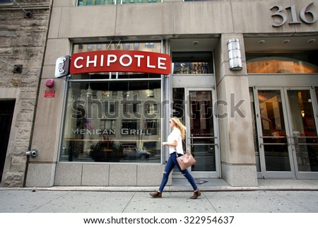 CHICAGO - FRIDAY, SEPTEMBER 25, 2015: Pedestrians walk past a Chipotle Mexican fast food restaurant.  Chipotle Mexican Grill, Inc. is a chain of restaurants. - stock photo