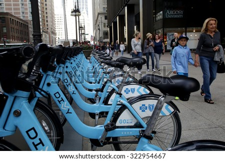 CHICAGO - FRIDAY, SEPTEMBER 25, 2015: Pedestrians walk past a Divvy bike rack. Divvy is a bicycle sharing system located in the City of Chicago.  - stock photo