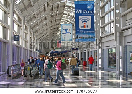 CHICAGO, IL - AUGUST 21, 2006: Unidentified Travelers walk to gates at Chicago O'Hare International Airport in USA. It was the 5th busiest airport in the world with 66,883,271 passengers in 2013. - stock photo