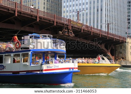 CHICAGO - JULY 4: Two Chicago Architectural Tour boats travel side-by-side along the Chicago River on July 4, 2015 in downtown Chicago, Illinois USA. - stock photo