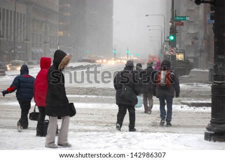 """CHICAGO - MARCH 31: Pedestrians crossing Michigan Avenue during the great """"snonaumi"""" blizzard on March 31, 2012 in Chicago, IL. The blizzard left many motorists stranded on Lake Shore Drive.  - stock photo"""