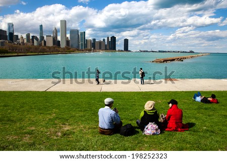 CHICAGO - May 4, 2014: People sit on the lawn of the Field Museum looking out over Lake Michigan and the cities skyline on one of the first warm days of spring, May 4, 2014, Chicago, Illinois.  - stock photo