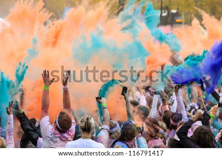 CHICAGO - OCTOBER 14: Chicago Color Run 5k race to benefit breast cancer research on October 14, 2012. Runners are given packets of colored powder to be thrown into the air throughout the race. - stock photo