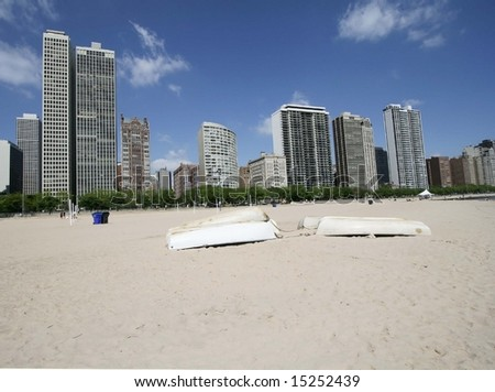 Chicago skyline and beach with boats on sand - stock photo