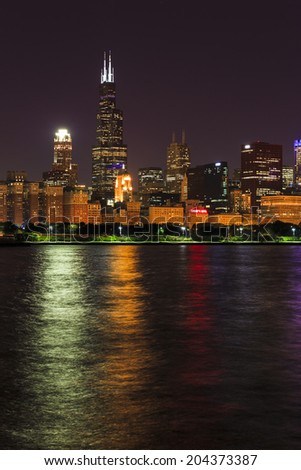 Chicago Skyline at night, reflected in Lake Michigan - stock photo