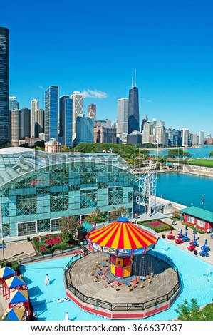 Chicago: wave swinger at Navy Pier and skyline with the John Hancock Center on September 22, 2014. Navy Pier was built in 1916, known as the famous landmark. The John Hancock Center is 1127 feet high - stock photo