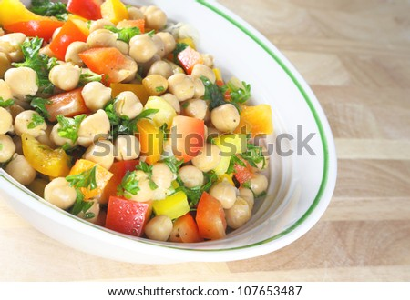 Chick pea salad in a bowl sitting on a wooden table. - stock photo