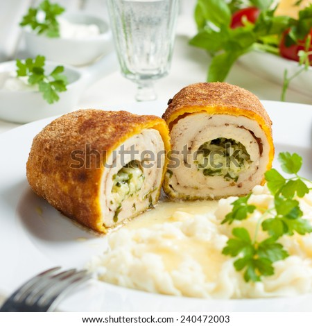 chicken and chicken Kiev with mashed potatoes.  Chop chicken fillet stuffed with juicy butter, cheese and greens on a white plate - stock photo