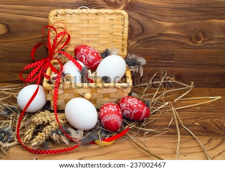 Chicken and Easter eggs in a basket on wooden background. - stock photo