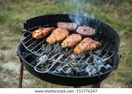 Chicken and hamburger patties on a grill - stock photo